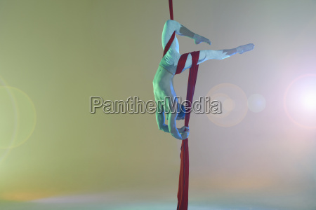 aerial dancer with red ribbon upside