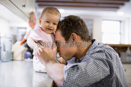 father with baby daughter in kitchen