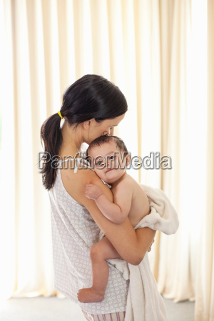 mother hugging baby girl after bath