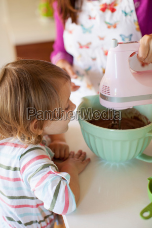 girl baking with mother in kitchen