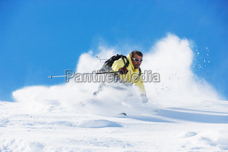 male skier speeding down mountain