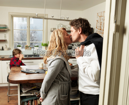 mature couple kissing in kitchen