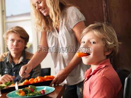 boy holding carrot in his mouth