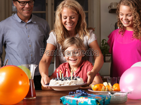 mother giving boy birthday cake at