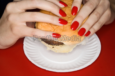 woman with red fingernails holding burger