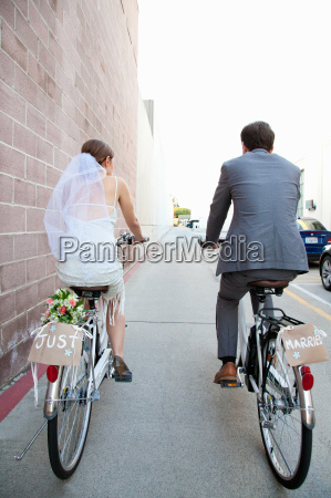 young newlywed couple cycling along street