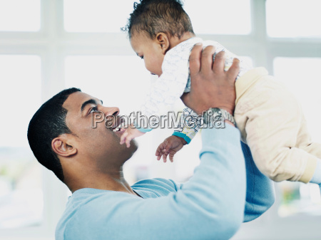 father lifting baby boy