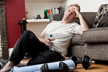 mid adult man leaning against sofa