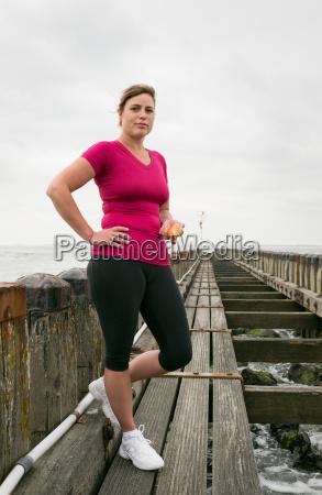 woman standing on pier wearing sports