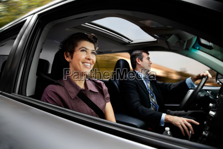 businessmen and women haring car to