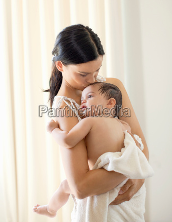 mother kissing baby girl at bathtime