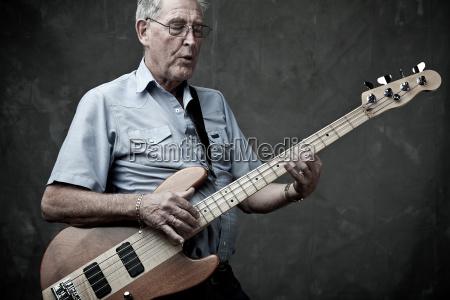senior man playing bass guitar