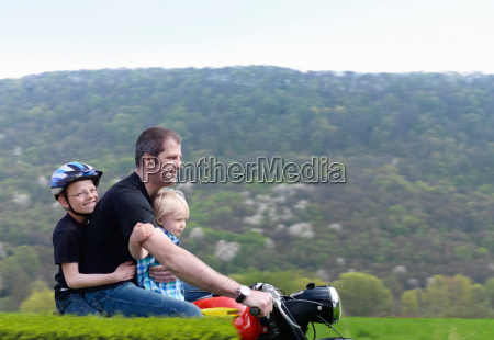 mature man riding motorbike with sons