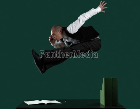 business man jumping over desk