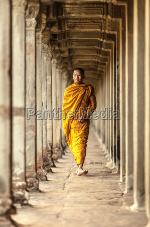 young buddhist monk walking through temple