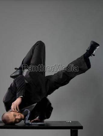 business man balancing on table