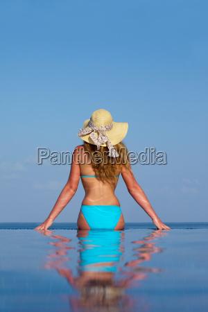 woman sitting in infinity pool