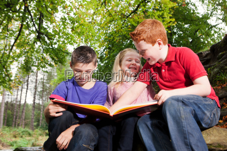 three children looking at a book