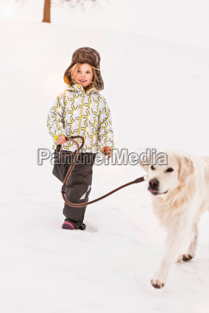girl walking dog in snow