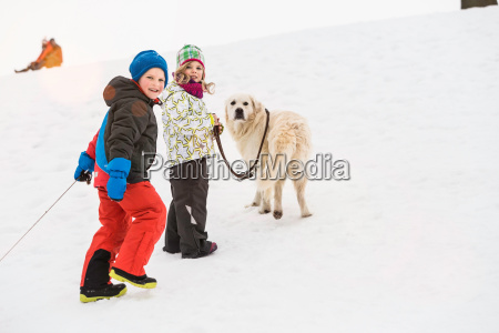 boy and girl walking dog in