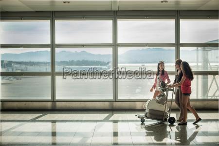 teenage girls and woman pushing luggage