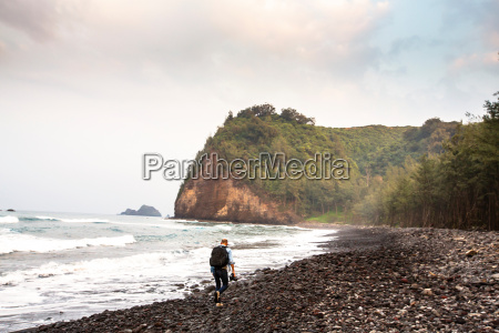 mid adult man hiking along beach