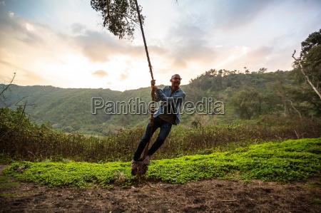 mid adult man on rope swing