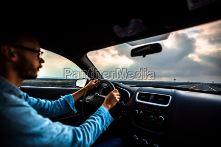 mid adult man driving car