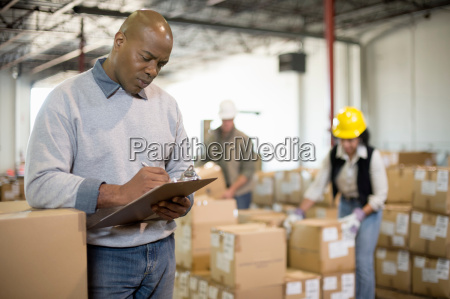 male warehouse worker holding clipboard