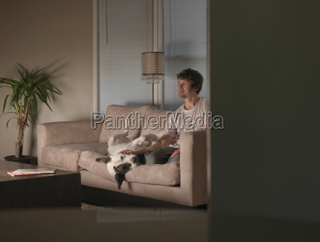 man and dog on couch watching