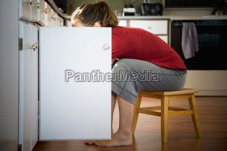 woman looking in kitchen cupboard