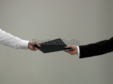 business man handing folder to colleague