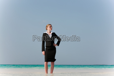 businesswoman standing on tropical beach