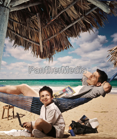 father and son relaxing on beach