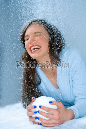 woman laughs in snow holds snowball