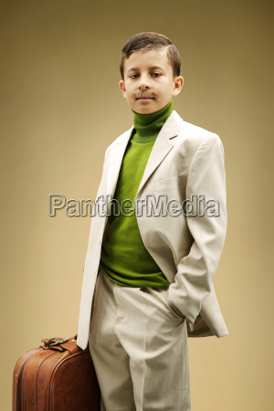 young boy dressed in beige suit