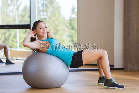smiling woman with fit ball flexing