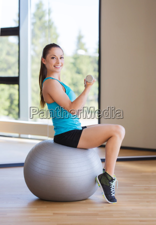 smiling woman with dumbbells and exercise