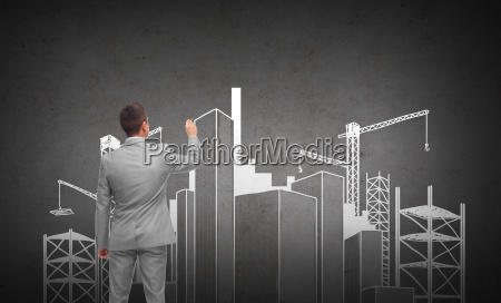 businessman drawing city construction site