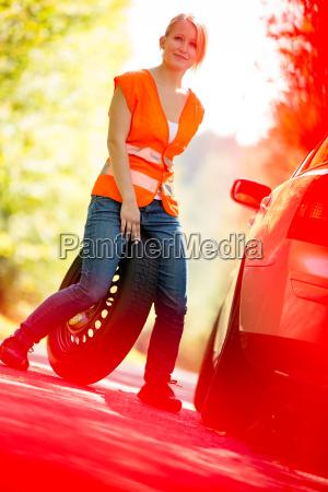 junge weibliche fahrer nach ihrem auto