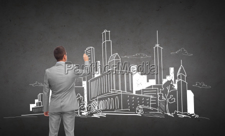 businessman drawing city sketch from back
