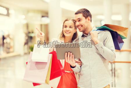 paar mit tablet pc und einkaufstaschen