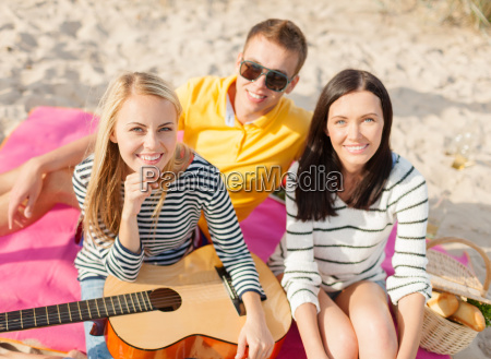 group of happy friends playing guitar