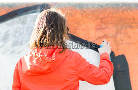 woman drawing graffiti with spray paint