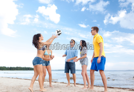 group of happy friends playing beach
