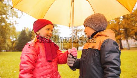 happy boy and girl with umbrella