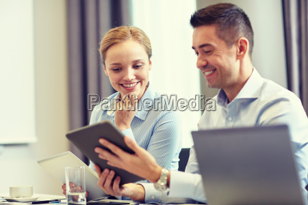 smiling business people with tablet pc
