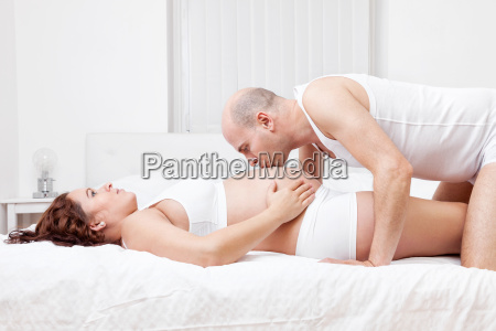delighted young parents in bed expecting