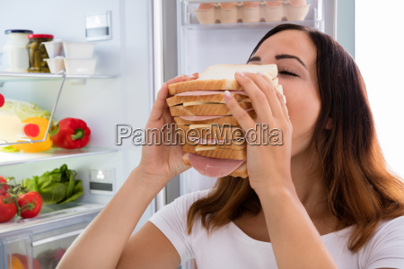 woman eating sandwich in front of