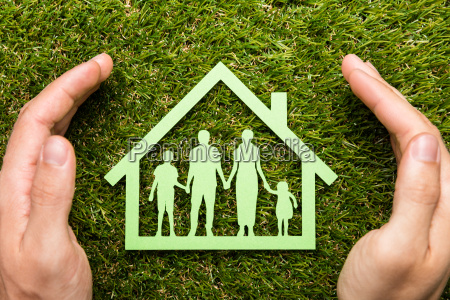 person hand protecting family home